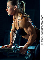 Woman bodybuilder - Young woman bodybuilder with dumbbell.
