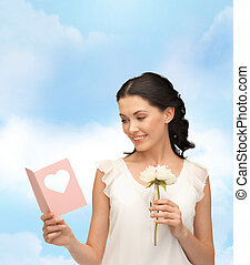 young woman holding flower and postcard - picture of young...