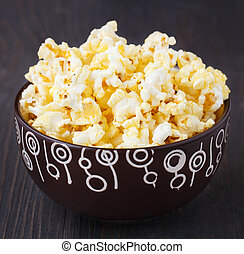 Fresh popcorn in bowl on a wooden table