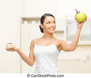 sporty woman with apple and cake in kitchen - sport and diet...