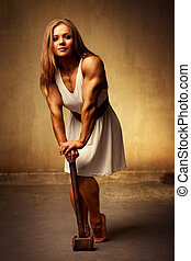 Young woman bodybuilder with hammer Ancient style