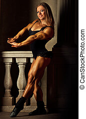 Young woman bodybuilder on ancient background