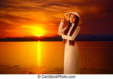 Young vietnamese woman on sunset background