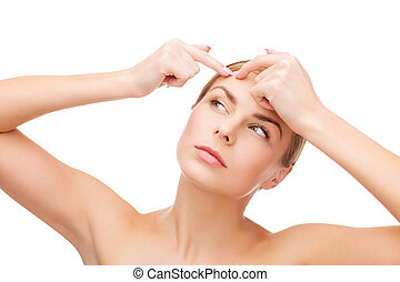young woman squeezing acne spots - health and beauty concept...