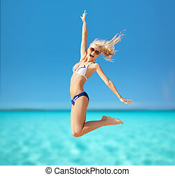 woman jumping on the beach - summer holidays, vacation and...