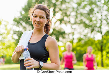 Healthy girl holding a water bottle - Athlete drinking water...