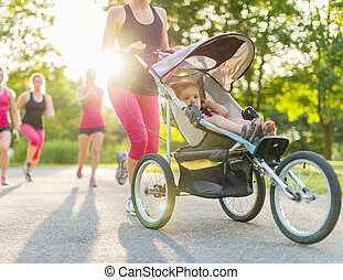 active mother jogging - Woman pushing her toddler while...