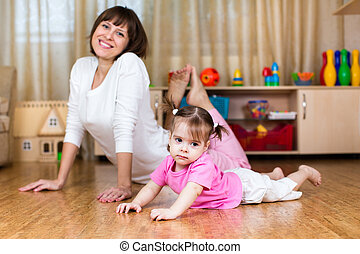 Mother and her child doing exercises together in home interior
