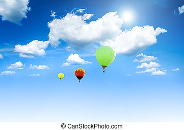 Balloons sunlit against a blue sky and clouds.