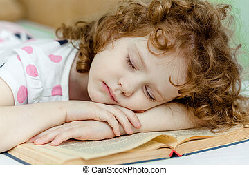 Portrait of a girl asleep reading a book.