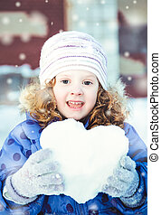 Beautiful little girl happily holding a snowball in the...