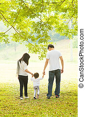 Parents and daughter having fun and walking on green lawn -...