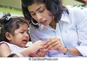 Crying girl with injured finger. - Indian family outdoor....