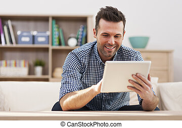 Smiling handsome man using digital tablet at home