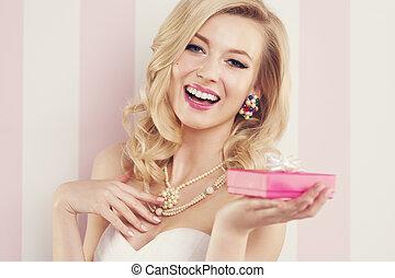 Elegant blonde woman holding pink gift