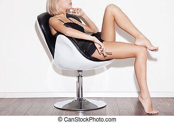 Gorgeous beauty in chair. Side view cropped image of...