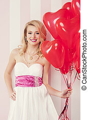 Smiling retro woman with red balloons in heart shape