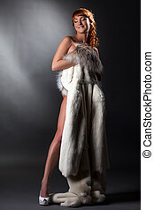 Pretty smiling nude girl posing with fur coat