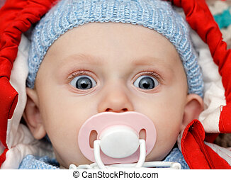 baby with dummy, looks funny - baby with dummy making a...