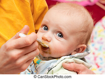 baby eating from a spoon