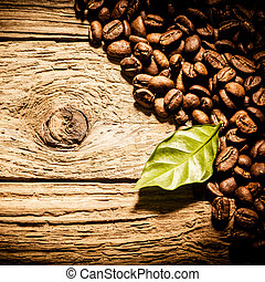 Full roast coffee beans with a fresh green leaf aarranged as...