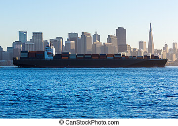San Francisco Skyline with merchant ship cruising bay at...