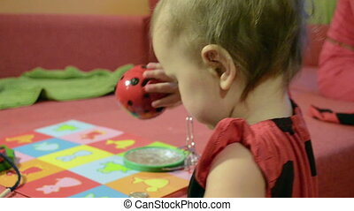 Baby in ladybird costume plays with porcelain toy