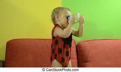 Baby in ladybird costume drinks from bottle on the couch