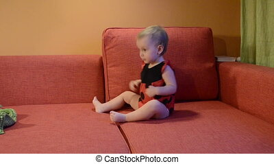 Baby in ladybird costume plays on the couch