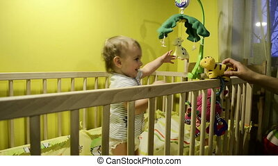 Child in the crib playing with a toy tiger