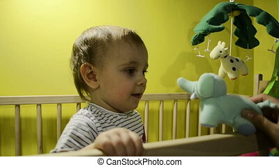 Child in the crib playing with a toy elephant