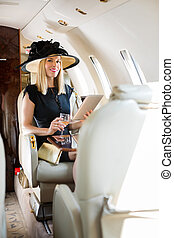 Woman With Digital Tablet And Drink Glass In Private Jet -...