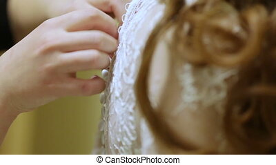 Doing up wedding dress - Bridesmaid helps to lace wedding...