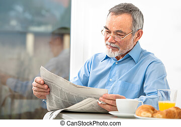 Senior man with a newspaper - Senior man with glasses...