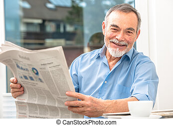 Senior man with a newspaper - Happy senior man at breakfast...