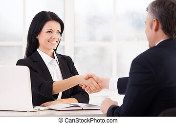 Sealing a deal Two cheerful business people handshaking and...