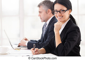 Business people at work Cheerful young businesswoman sitting...
