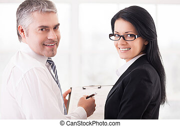 Business people doing paperwork. Two smiling business people...