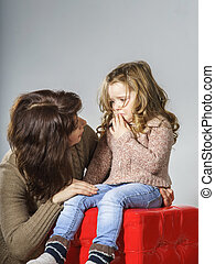 Mother reassuring little daughter. She is distracted and...