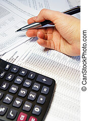 Office table with calculator, pen and accounting document -...