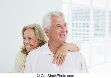 Happy senior woman embracing man from behind