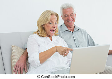 Cheerful senior couple using laptop at house - Cheerful...