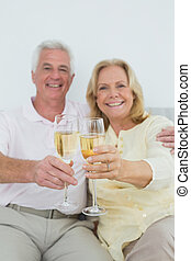 Senior couple holding out champagne flutes at home -...