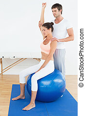Woman on yoga ball while working with physical therapist -...