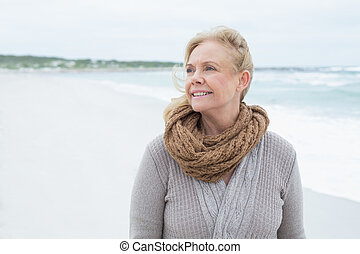 Contemplative senior woman looking away at beach -...