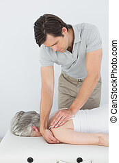 Male physiotherapist massaging a senior woman's shoulder in...