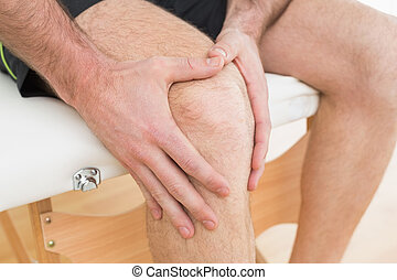 Mid section of a man with his hands on a painful knee -...