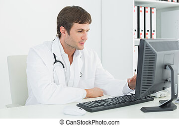 Male doctor using computer at medical office - Concentrated...