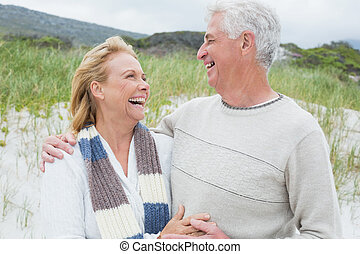 Cheerful senior couple looking at each other at beach