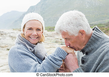 Senior man kissing happy woman's hand - Side view of a...
